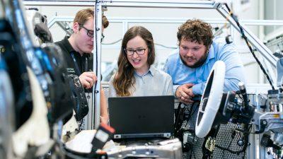 Zwei Mitarbeiter und eine Mitarbeiterin (in der Mitte) beobachten die technische Umsetzung am Laptop.