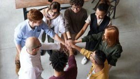 Menschen stehen im Kreis und machen gleichzeitig einen Handschlag