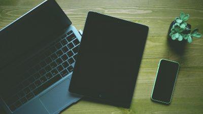 Laptop, Tablet und eine Pflanze stehen auf einem Schreibtisch.