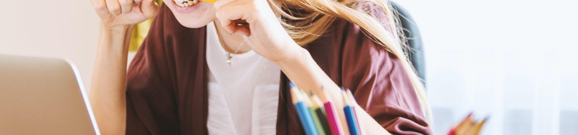 Eine Frau sitzt vor dem Laptop und beißt in ihren Stift.