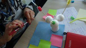 Man sieht einen Design-Thinking-Workshop. uf dem Bild ist ein gebastelter Prototyp aus blauem Filz und weißen Kugeln.