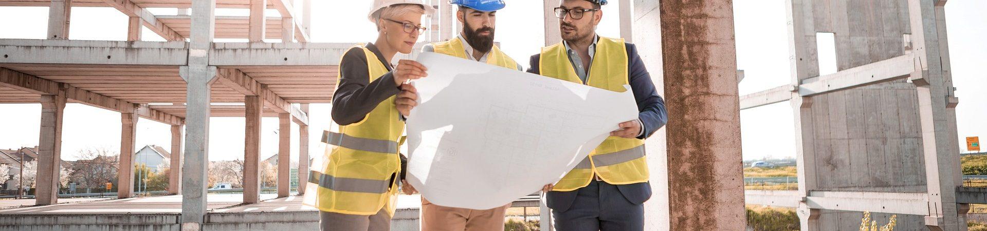 Drei Menschen mit Schutzhelm betrachten sich einen Bauplan auf einer Baustelle.