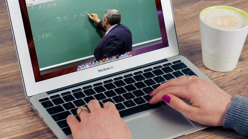 Frau sitzt am Laptop und bil.det sich digital