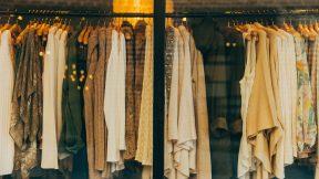 Nachhaltige Entwicklung: Verschiedene Textilien wie Pullover, Hemden oder Jacken für Frauen hängen an einem Schaufenster.