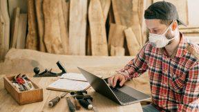 E-Leraning im Bauhandwerk. Ein Arbeiter schaut auf seinen Laptop.
