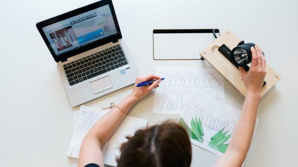 Frau sitzt am Schreibtisch für eine virtuelle Veranstaltung