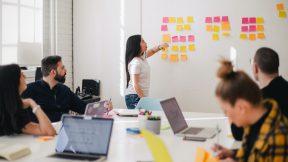 Ein Kommunikationsaudit: 7 Kollegen und Kolleginnen sitzen im Meetingraum und machen eine Auswertung. Dabei kleben Post-its an einer Tafel.