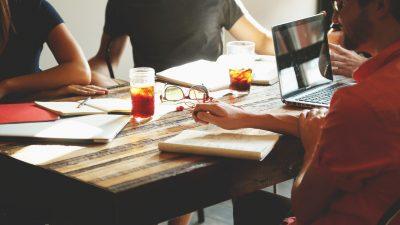 Brainstorming: 3 Kolleg/-innen sitzen an einem Tisch und überlegen sich eine Kommunikationsstrategie,