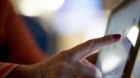 Eine Frau berührt mit ihrem Finger ein Tablet.
