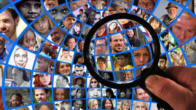 Viele Gesichter werden unter einer Lupe analysiert.