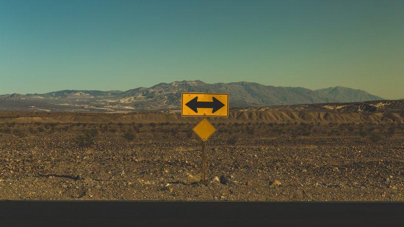 Ein gelbes Schild mit zwei schwarzen Pfelien zeigen die Richtung rechts und links an.