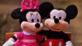 Mickey Mouse und Minie Mouse umarmen sich auf einer Parkbank.