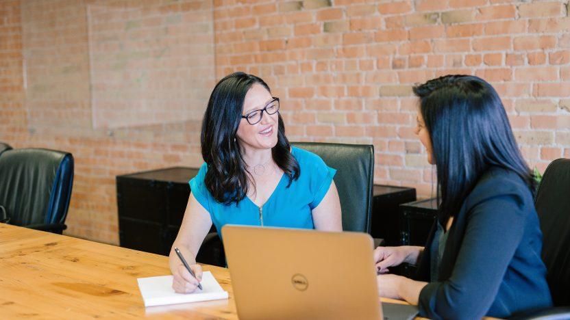 Zwei Frauen sprechen miteinander und sitzen vor einem Laptop.