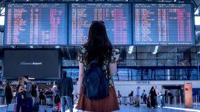 Eine Frau steht am Flughafen und schaut nach Abflügen.