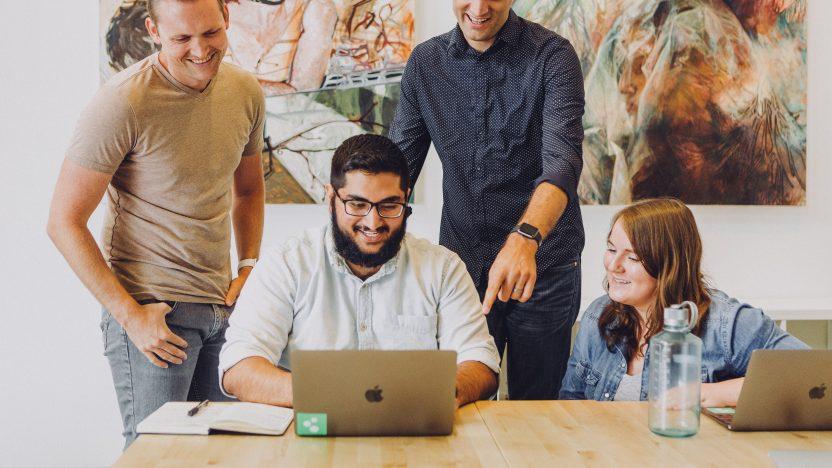 Vier Personen sitzen und stehen um ein Notebook herum und arbeiten gemeinsam an einem Projekt.