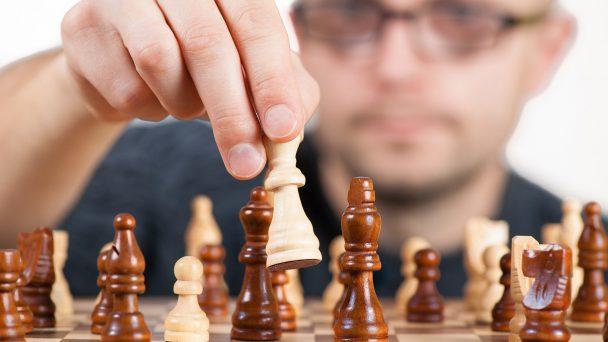 Ein Mann spielt das strategische Brettspiel Schach