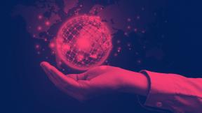 Ein roter Globus liegt auf einer Hand und soll die Nachhaltigkeit symbolisieren