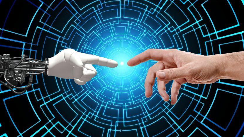 Zwei Zeigefinger berühren sich. Links ein Roboter-Finger, rechts ein menschlicher Zeigefinger