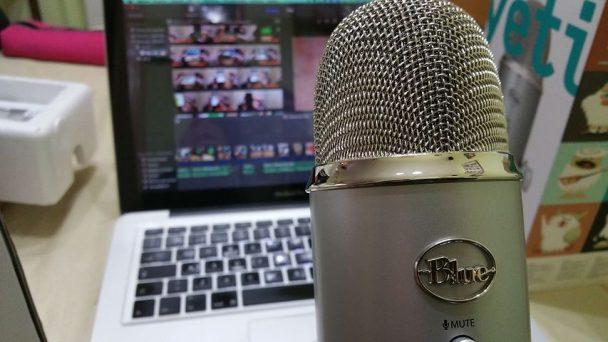 Auf einem Tisch stehen Podcast-Equipment. Mikrofon und Laptop.