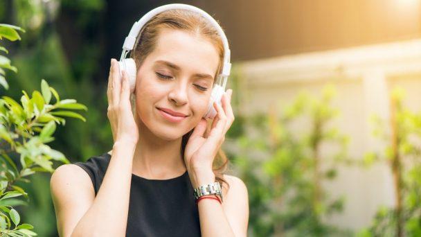 Frau mit Kopfhörer freut sich und hört dabei einen Podcast