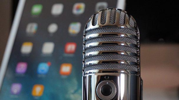 Ein Smartphone im Hintergrund und ein Mikrofon im Vordergrund soll einen Podcast symbolisieren, der digital aufgenommen wird und gehört wird.