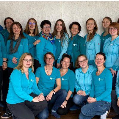 Auf dem Bild ist zu sehen: Das Team des Therapiezentrums balance in hellblauen Hemden und Logo und Hauptgebäude des Zentrums.