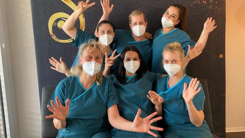 6 Frauen des Teams der Praxis Dr. Arnold posieren mit Mundschutz und grünen OP-Hemden.